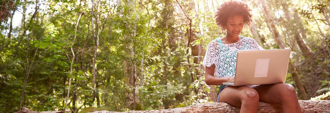 Vrouw met computer in het bos